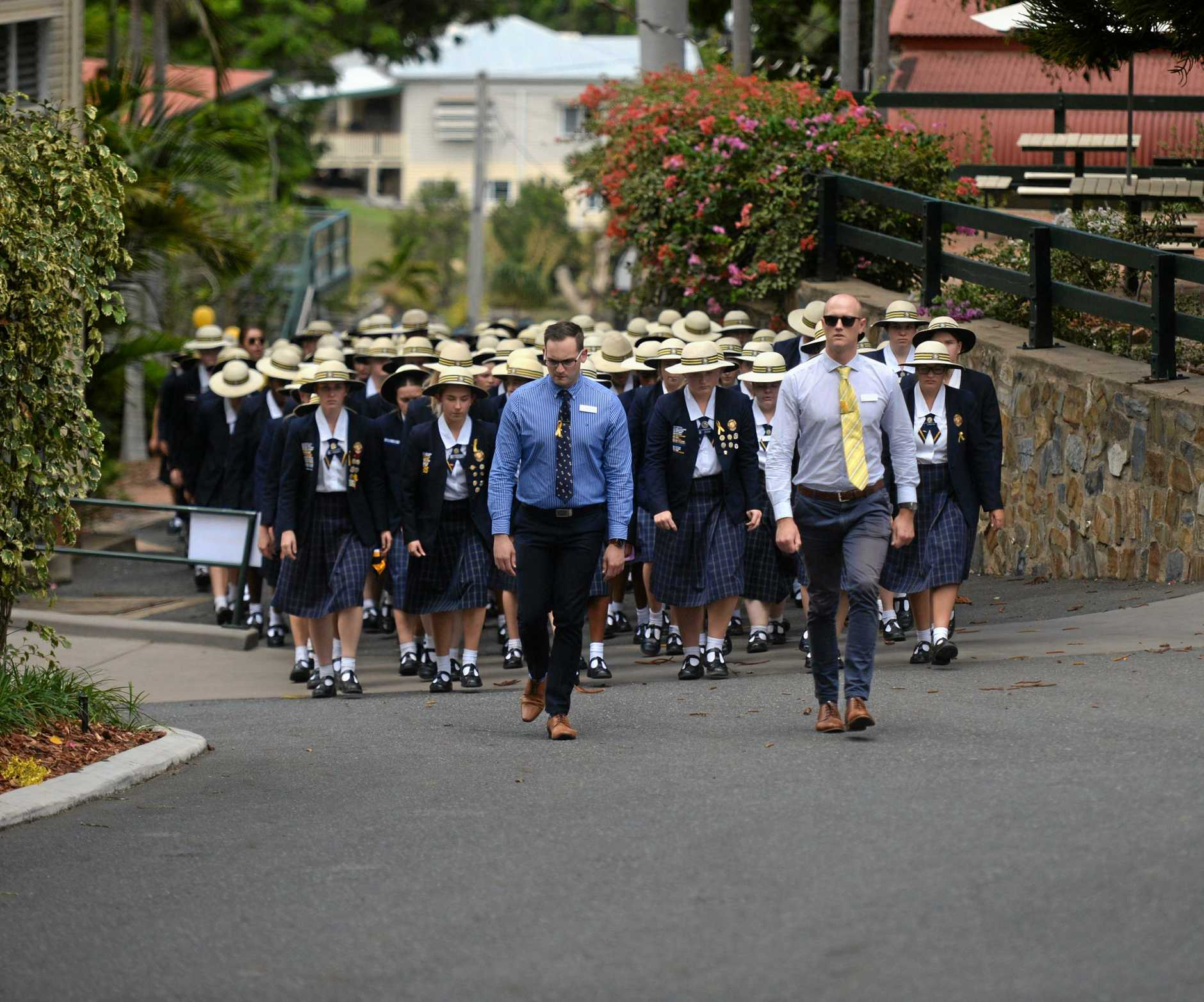 Rockhampton Girls Grammar School students march up to a service celebrating the lives of Bev and Olivia Harwood.
