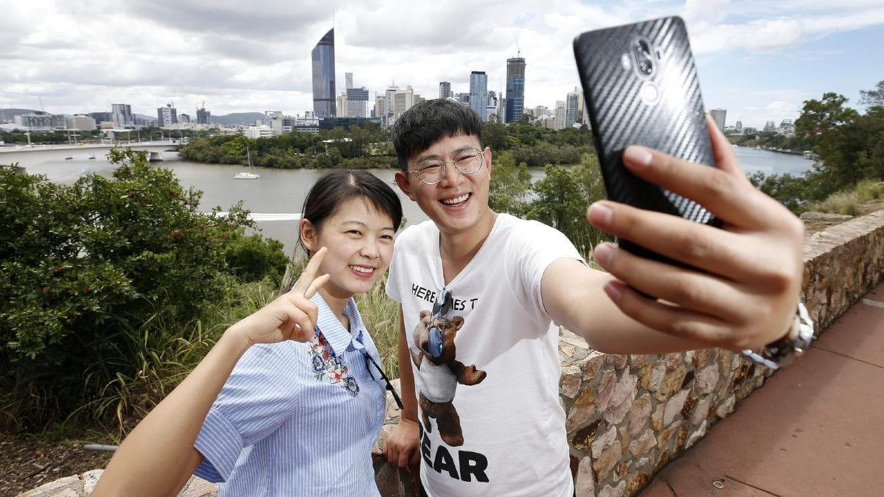 Miss Lee and Mr Pan from China take a selfie at the Kangaroo Point cliffs. Picture: Josh Woning/AAP