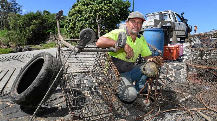 CLEANUP: Bundaberg Regional Council contractor Glenn Rumsey with some of the mountains of rubbish he has collected along the banks of the Burnett River over the past four weeks.