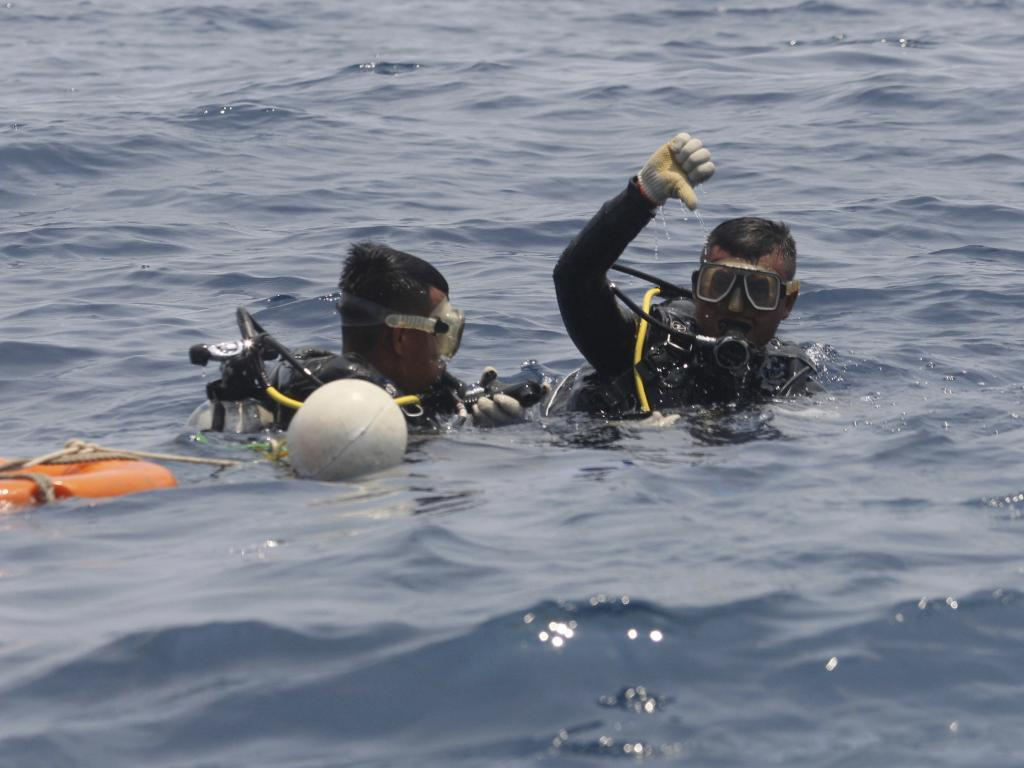 A navy diver on board a search vessel said his team found the orange cylinder containing the recorder among debris on the muddy sea floor. Picture: AP