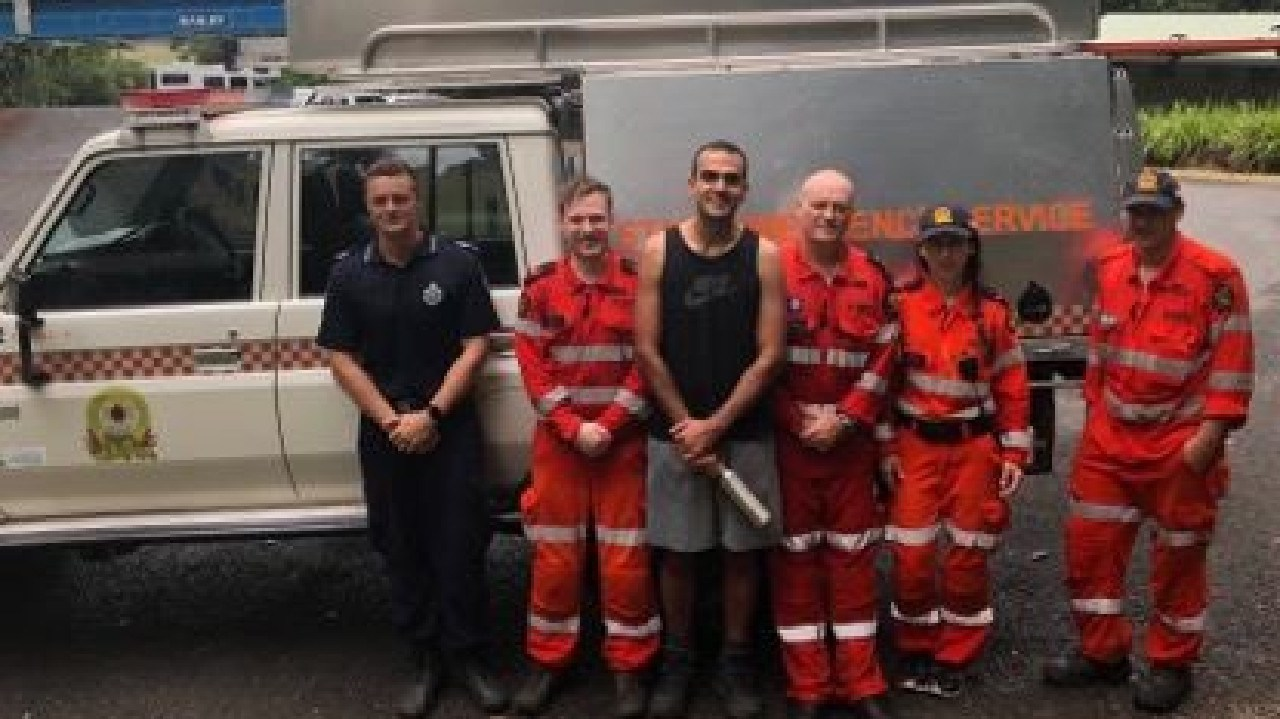 A 31-year-old Toowoomba man, centre, with his Queensland Police and SES rescuers. The man spent the night stuck at the top of Mount Bartle Frere after the weather closed in on him.