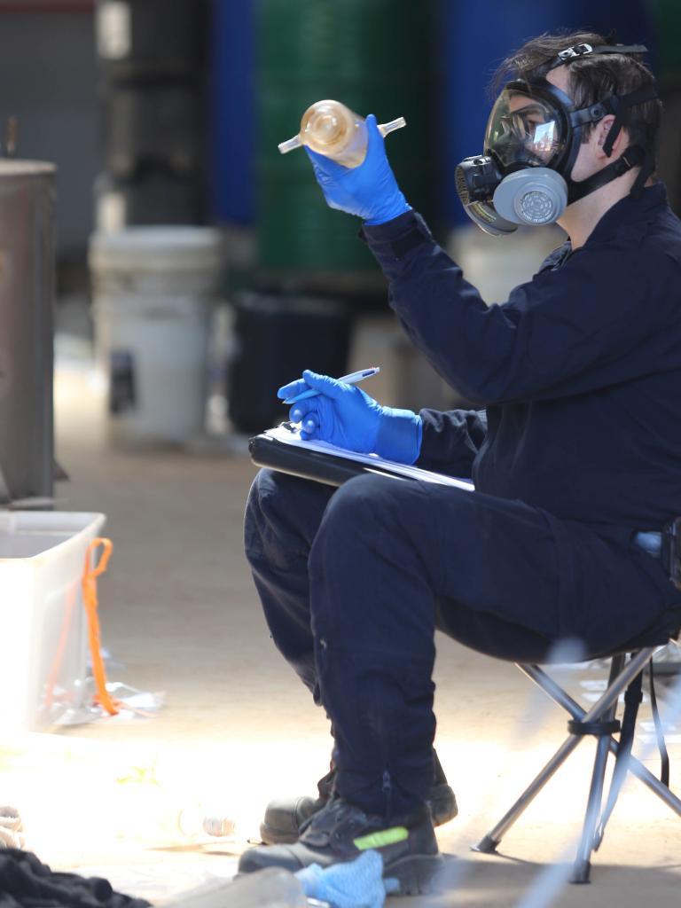 A police officer examines a piece of equipment found in the drug lab. Picture: NSW Police