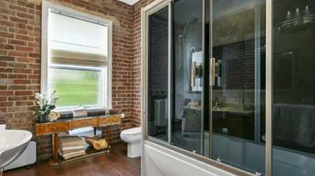 Exposed brick aligns with modern style in the bathroom.