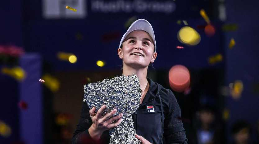 Ashleigh Barty of Australia holds the trophy after winning the women's singles final match against Wang Qiang.