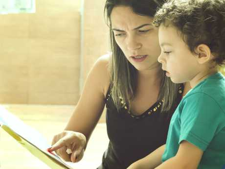 A young woman reading children's stories to her little two year old son.