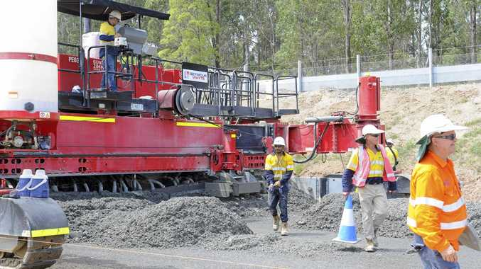 HARD WORK: Pacific Highway crews work with a paver that helps level the concrete that will become the new highway. The crews can complete  800-1200m a day.