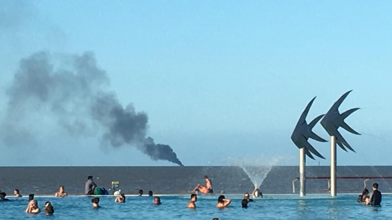 Smoke billowing from a burning motor cruiser can be seen from the Cairns Esplanade.