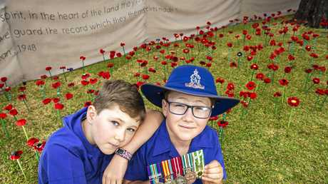 Rangeville State School students Fletcher (left) and Archie Milne with the Vietnam War service medals of their grandfather John Forbes at the 443 Poppies Project at the school for Remembrance Day, Thursday, November 8, 2018.