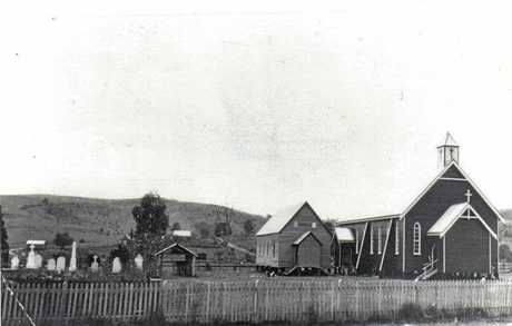 The original Zion Lutheran Church stands next to the current day church prior to being removed in the 1930s.