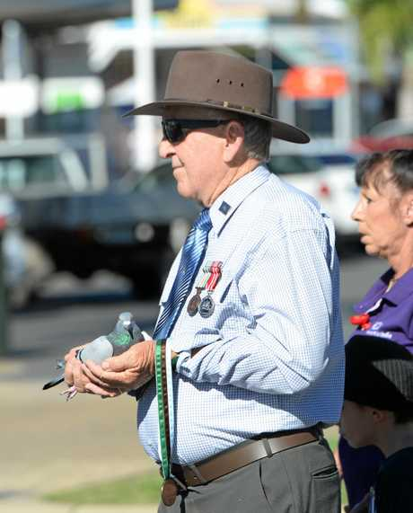 Cliff Gormley with marching with a pigeon during the Emu Park ANZAC Day parade.   Photo: Chris Ison / The Morning Bulletin