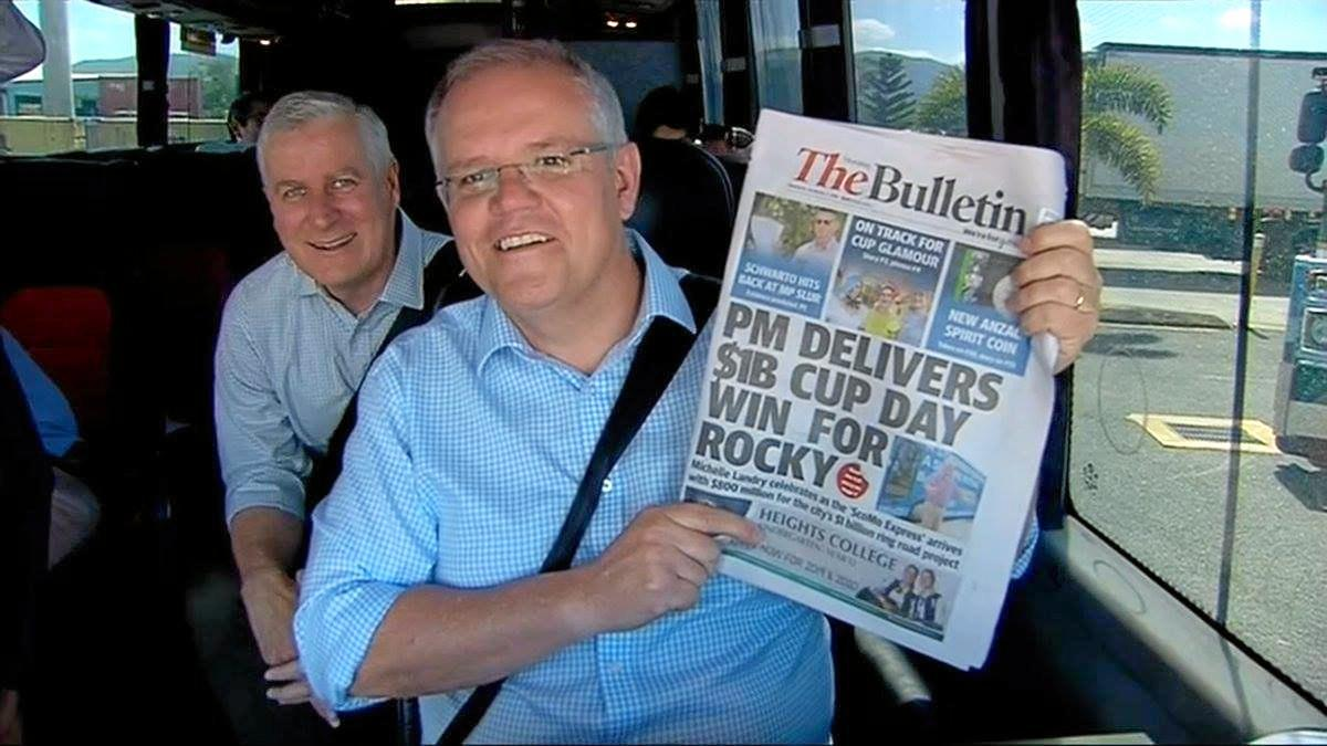 Prime Minister Scott Morrison with Deputy Prime Minister Michael McCormack aboard the big blue bus with a copy of the Bully.