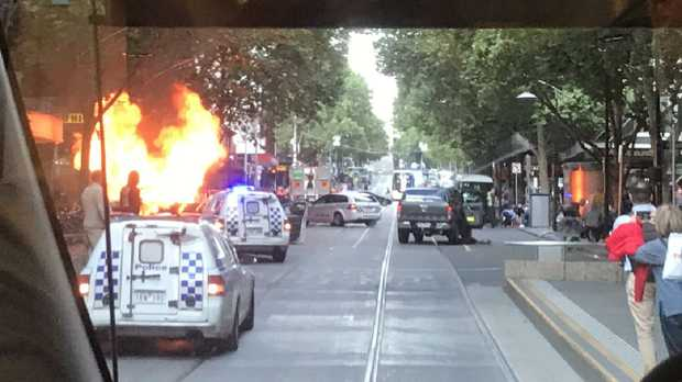 A car is alight as police attend to an incident on Bourke St. Picture: @meegslouise/Twitter