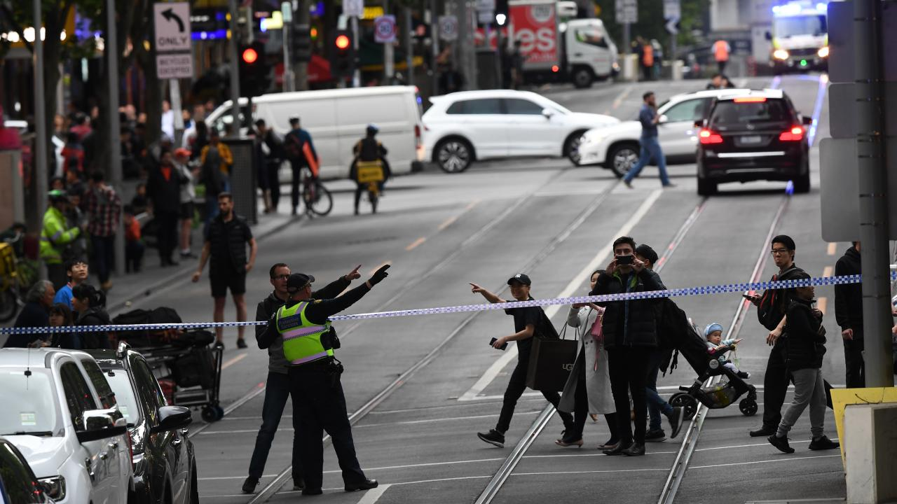 Police are seen redirecting pedestrians away from an incident on Bourke Street. Picture: James Ross/AAP