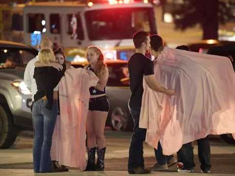 Young people comfort each other as they stand near the scene in Thousand Oaks, California. Source:AP