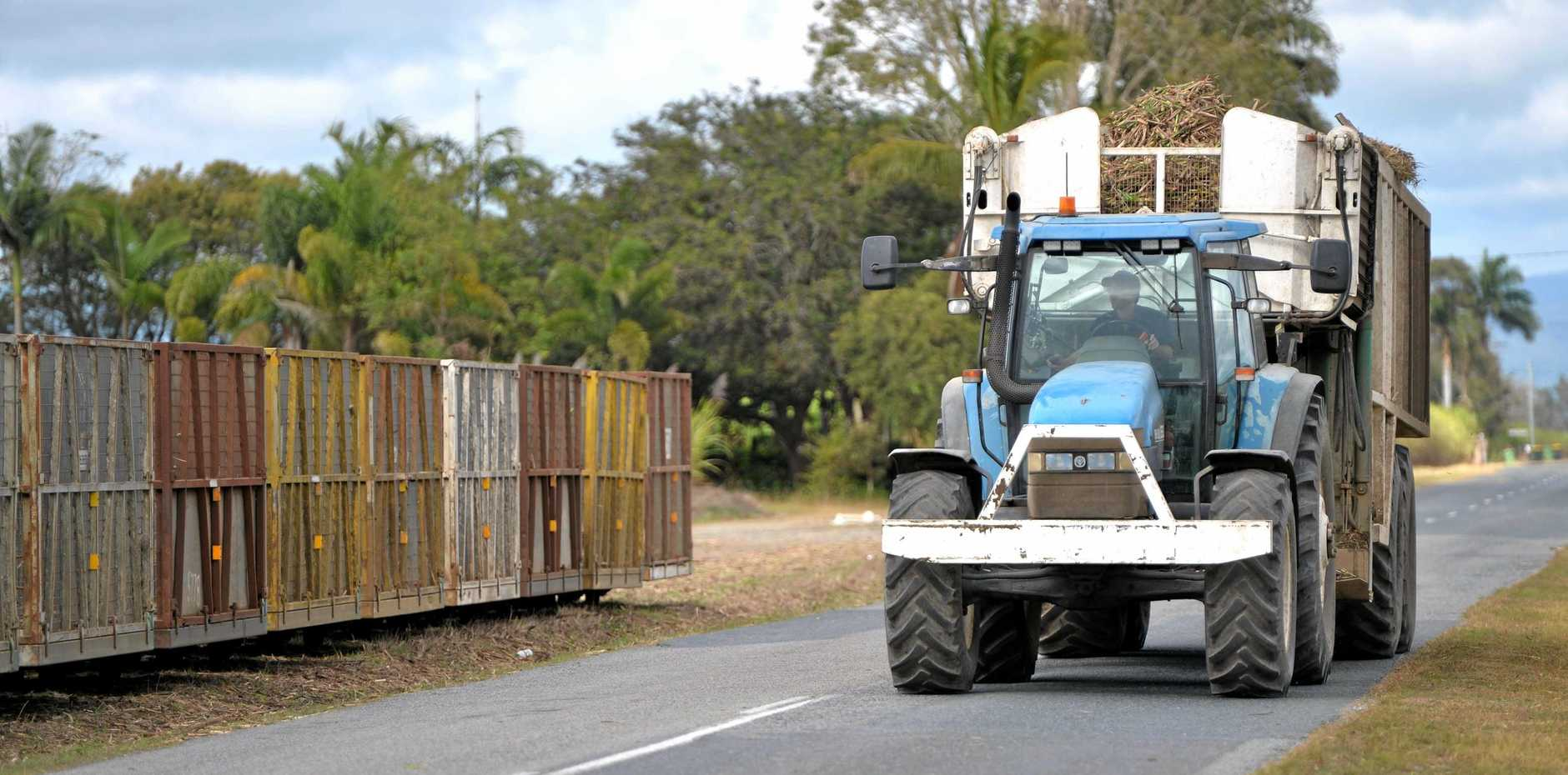 A tractor with a loaded bin about to pull up near bins to drop off it's load.