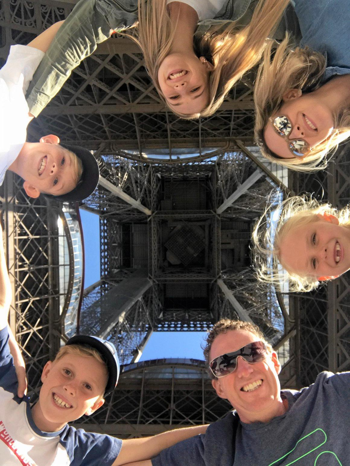 The Nicholl family stand under the Eiffel Tower in Paris, France.  From the top, clockwise is Kalia(16), Beth (Mum), Amaya (8), Nathan (Dad), Rase (10) and Tide (12).