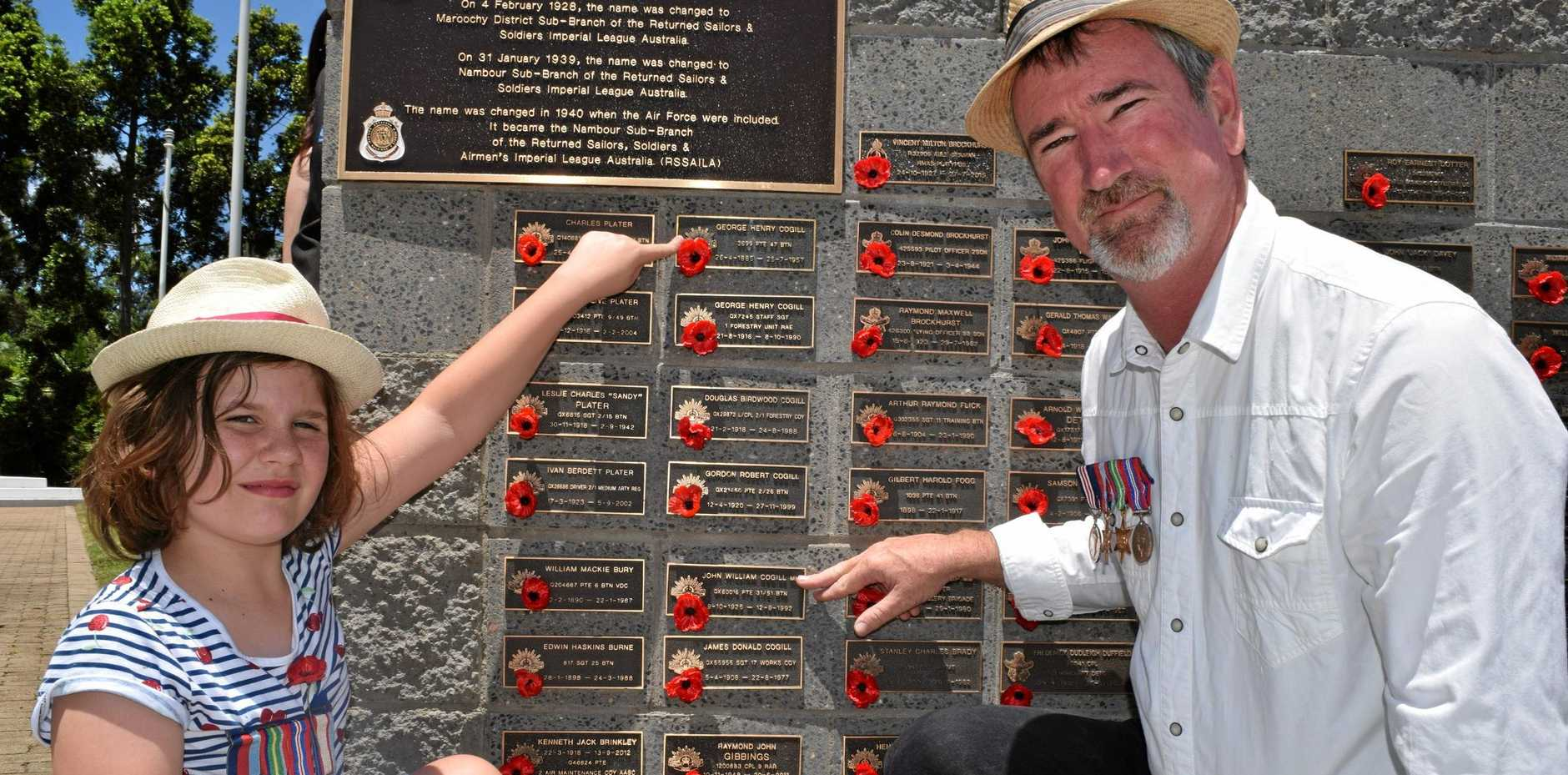 Opal Cogill, 9, with her father Ted remember six of their family members who served in wars as they attended the Remembrance Day ceremony at Quota Park, Nambour.