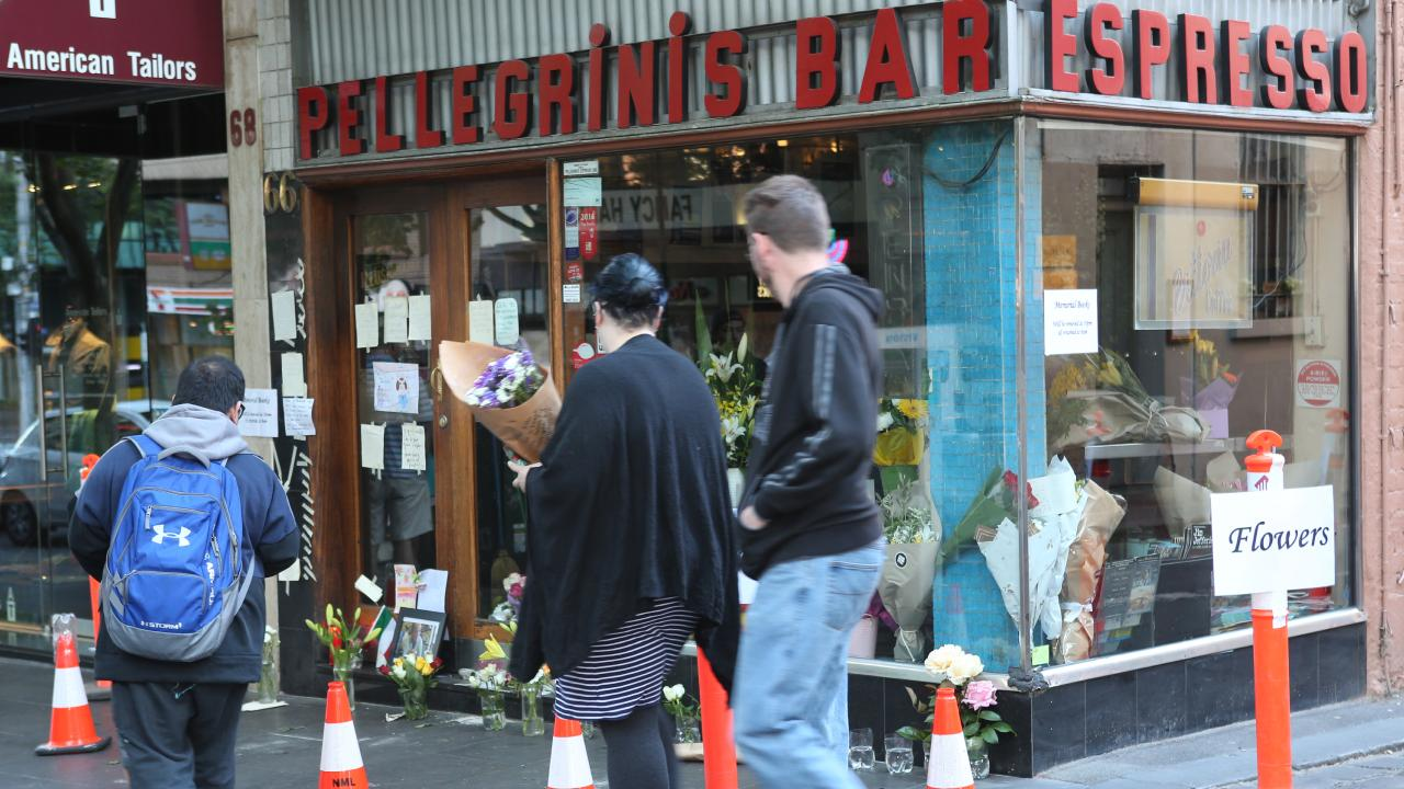 Mourners place flowers at the scene. Picture: David Crosling