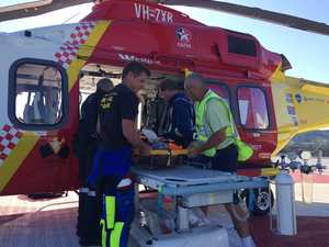Struggling swimmer saved by friends, winched off beach