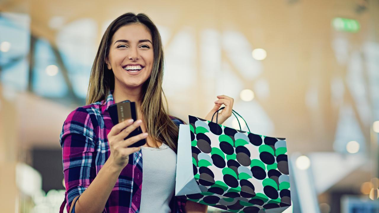 A woman holding up a credit card and shopping bags. Picture: iStock.