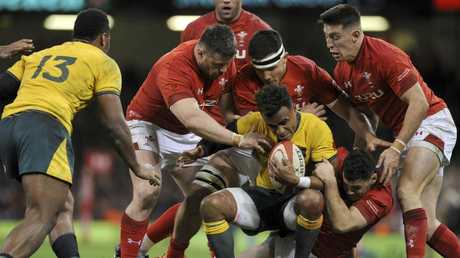 Will Genia is tackled by Welsh defenders during the Wallabies' historic defeat on Sunday morning. Picture: AP