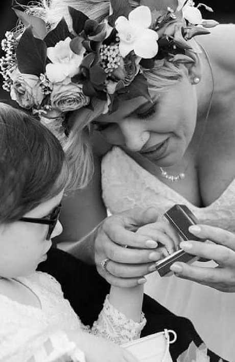 Paige Skarratts hands the ring to her mother Tania during their wedding ceremony at Lady Cilento Hospital.