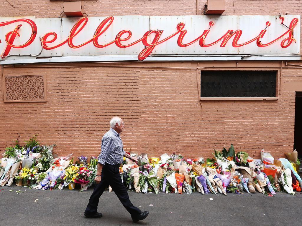 Nino Pangrazio walks past floral tributes at his cafe where co-owner Sisto Malaspino was killed on Friday. Picture: Michael Dodge/Getty Images