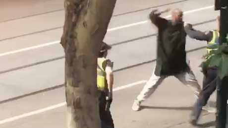 The Bourke St attacker pictured lunging at police with a knife after stabbing three people, killing one.