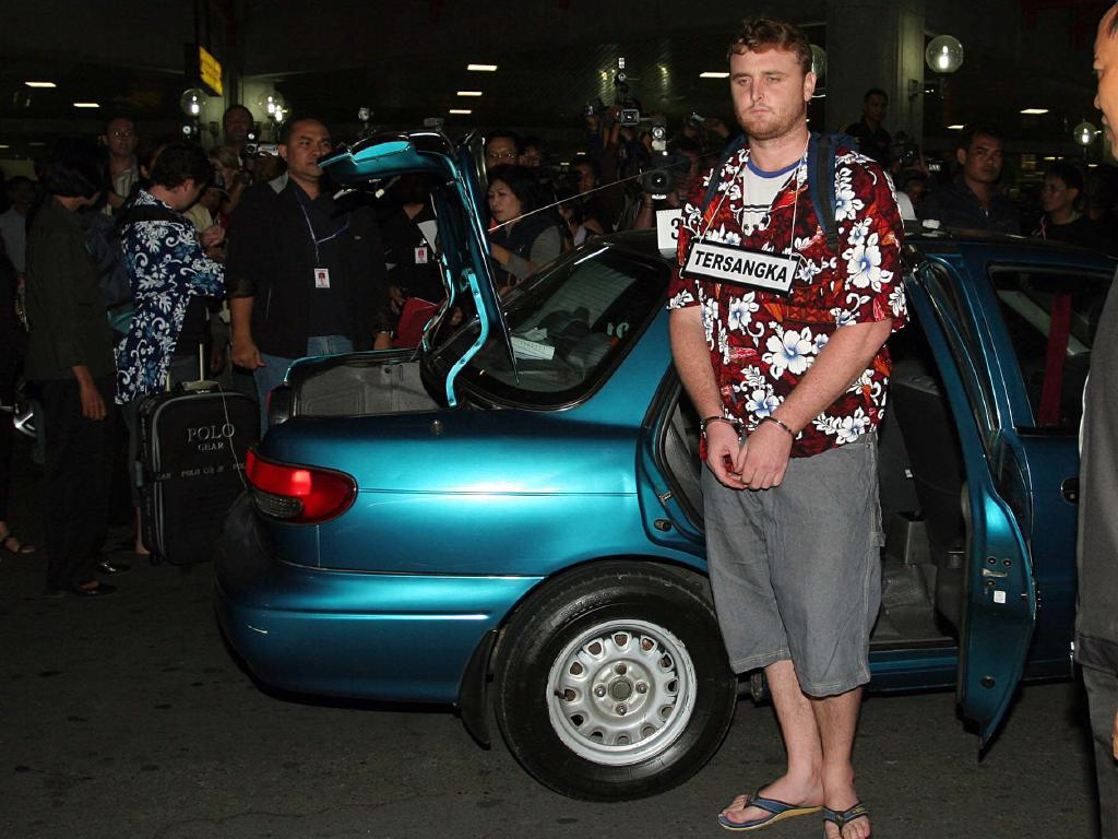 Martin Stephen handcuffed and Renae Lawrence arrive at Ngurah Rai airport for the re-enactment of their heroin arrest. Picture: Lukman S Bintoro.