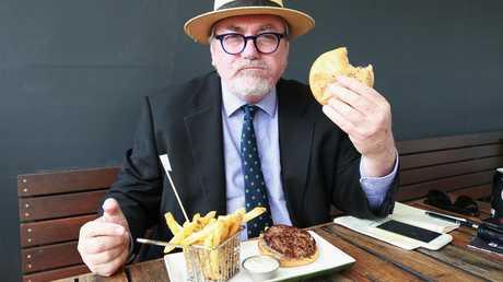Des Houghton tries the Big Pac burger at Burger Urge. (AAP Image/Claudia Baxter)