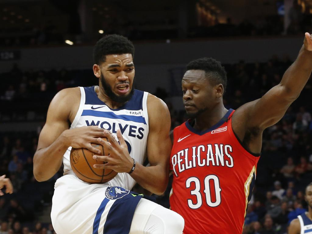 The Minnesota Timberwolves' Karl-Anthony Towns, left, drives on New Orleans Pelicans' Julius Randle during the first half. Picture: Jim Mone/AP
