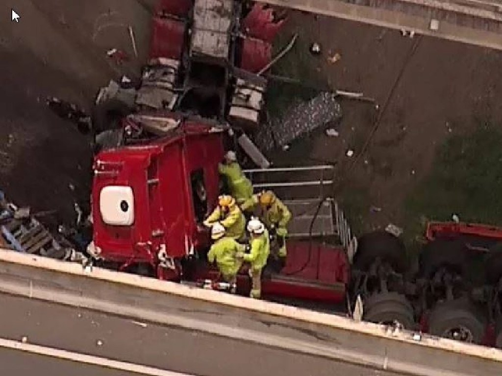 Rescue crews work to rescue the driver of the crashed truck. Picture: Channel 9