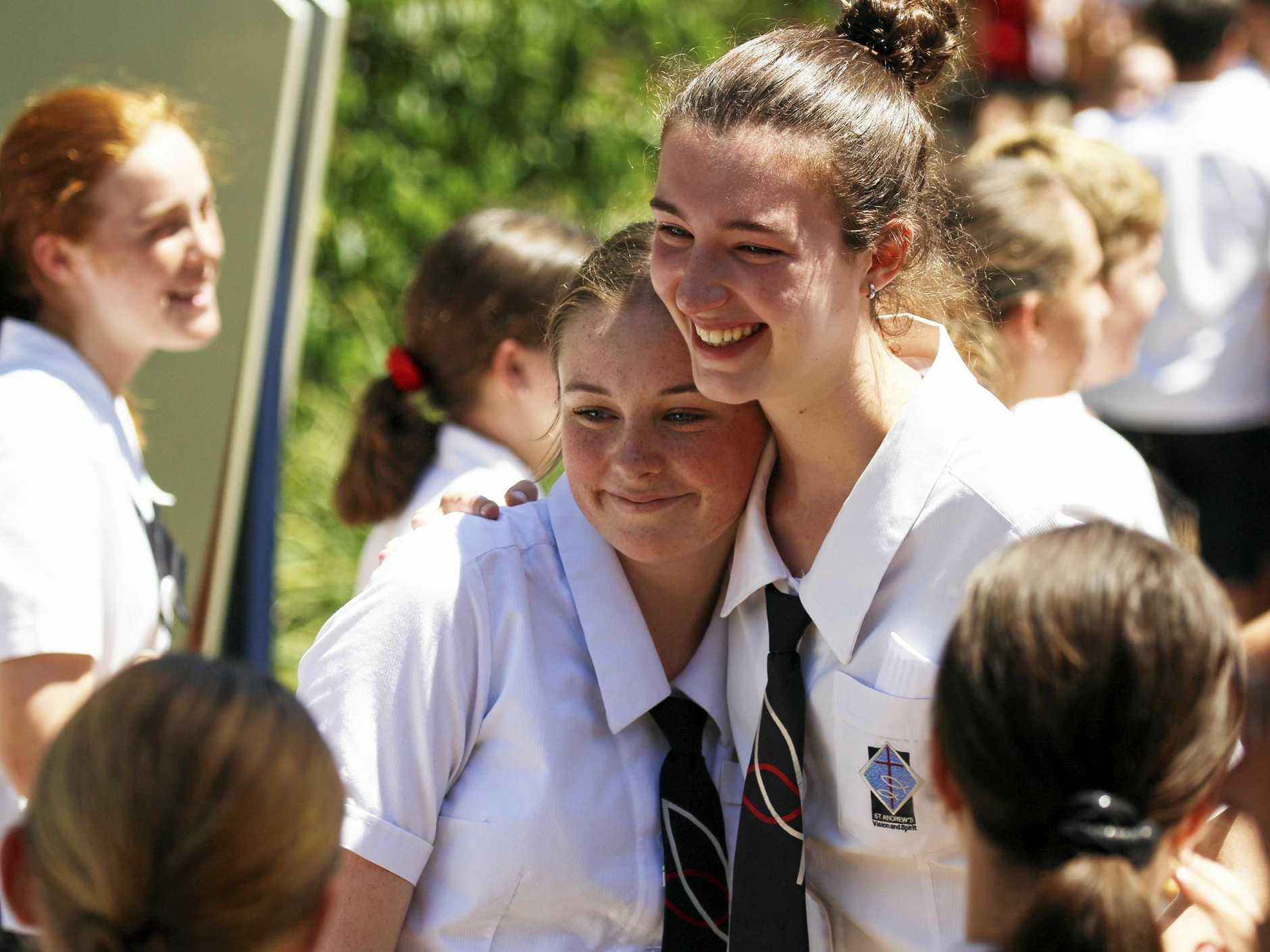Graduates Jaimee Watson and Darcy Condon hugging in the guard of honour.