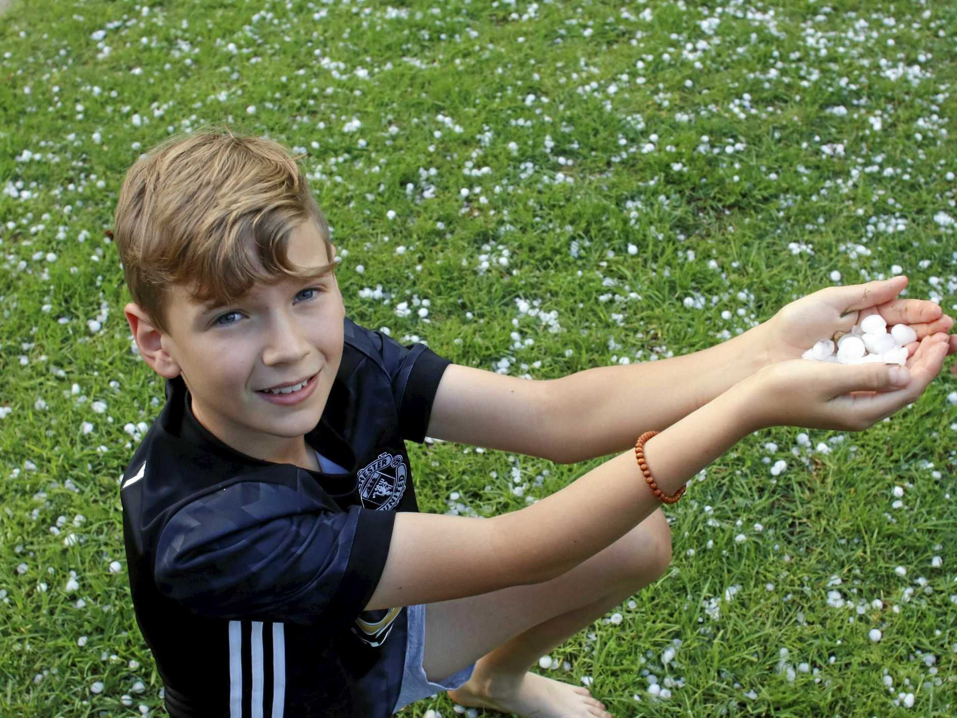 SPOT OF HAIL: Quinn Farmer collects hail after it fell in Rangeville last year.