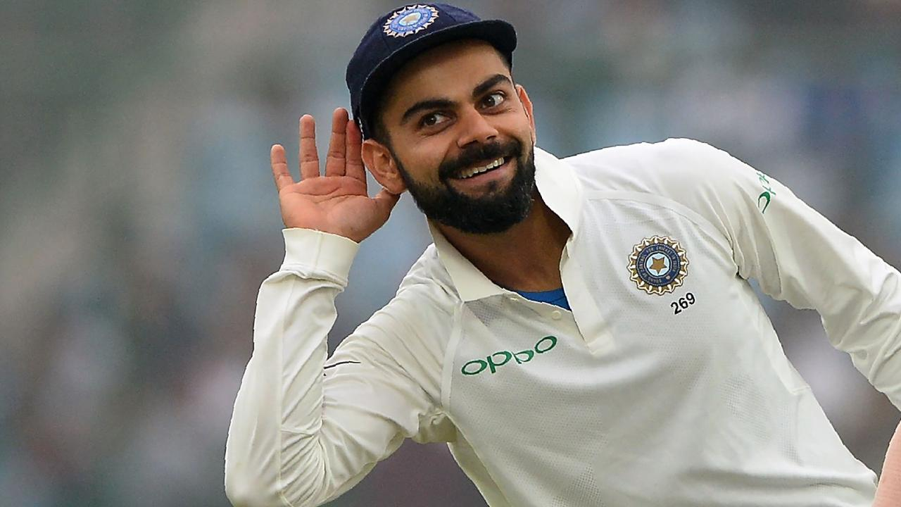 (FILES) This file photo taken on December 5, 2017 shows Indian team captain Virat Kohli (L) gesturing towards the crowd as teammate Shikhar Dhawan looks on during the fourth day of third Test cricket match between India and Sri Lanka at the Feroz Shah Kotla Cricket Stadium in New Delhi. Man of the series Virat Kohli plundered runs and records in all three matches. Nicknamed King Kohli, the prolif