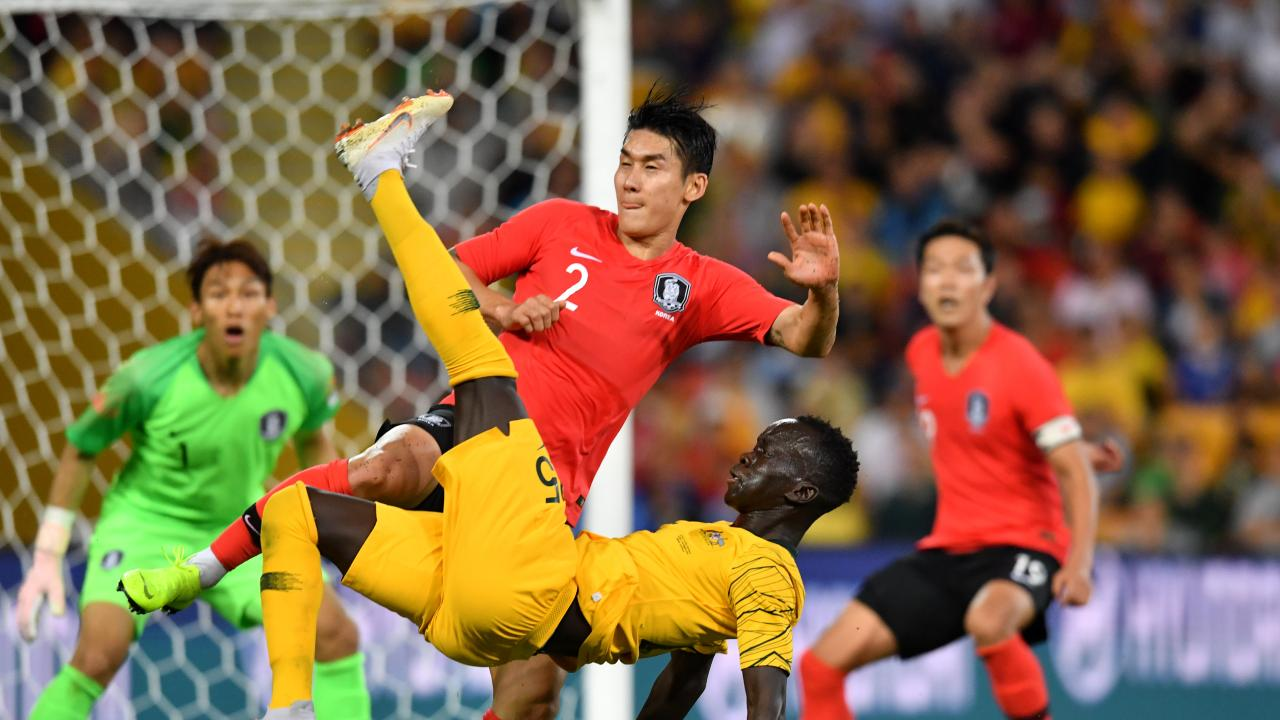 Awer Mabil (centre) of the Socceroos does an over head kick