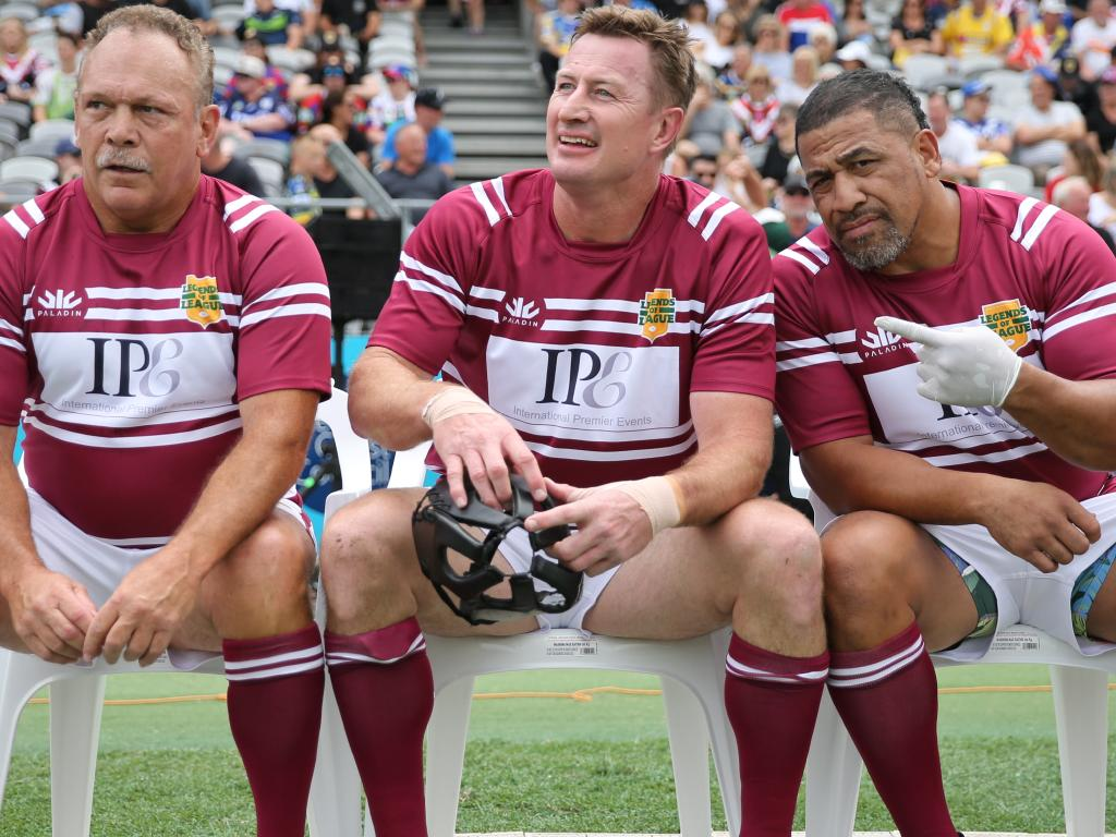 Hopoate gives the cameras the finger while sitting on the sideline alongside Manly legends Cliff Lyons and Steve Menzies. Picture: Tim Hunter