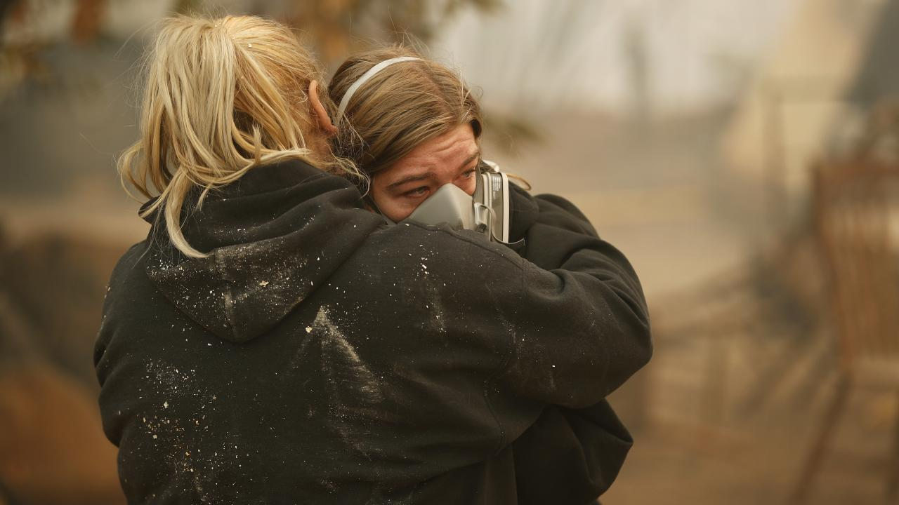 Krystin Harve comforts her daughter Araya Cipollini at the remains of their home in Paradise, California. Picture: AP