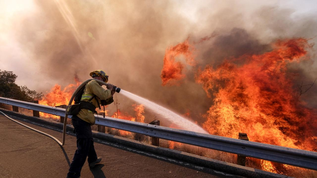 A firefighter battles a fire along the Ronald Reagan Freeway in Simi Valley, California. Picture: AP