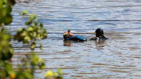 Divers scour through the creek for mystery evidence. PICTURE: STEWART MCLEAN
