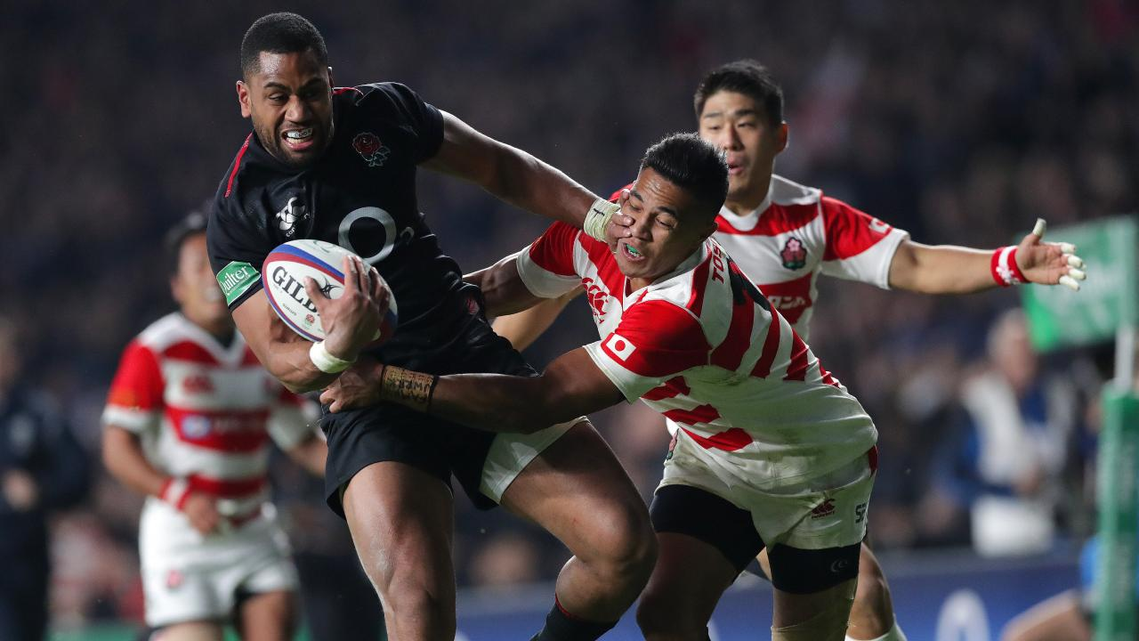 Joe Cokanasiga of England tries to fend off Kenki Fukuoka of Japan.