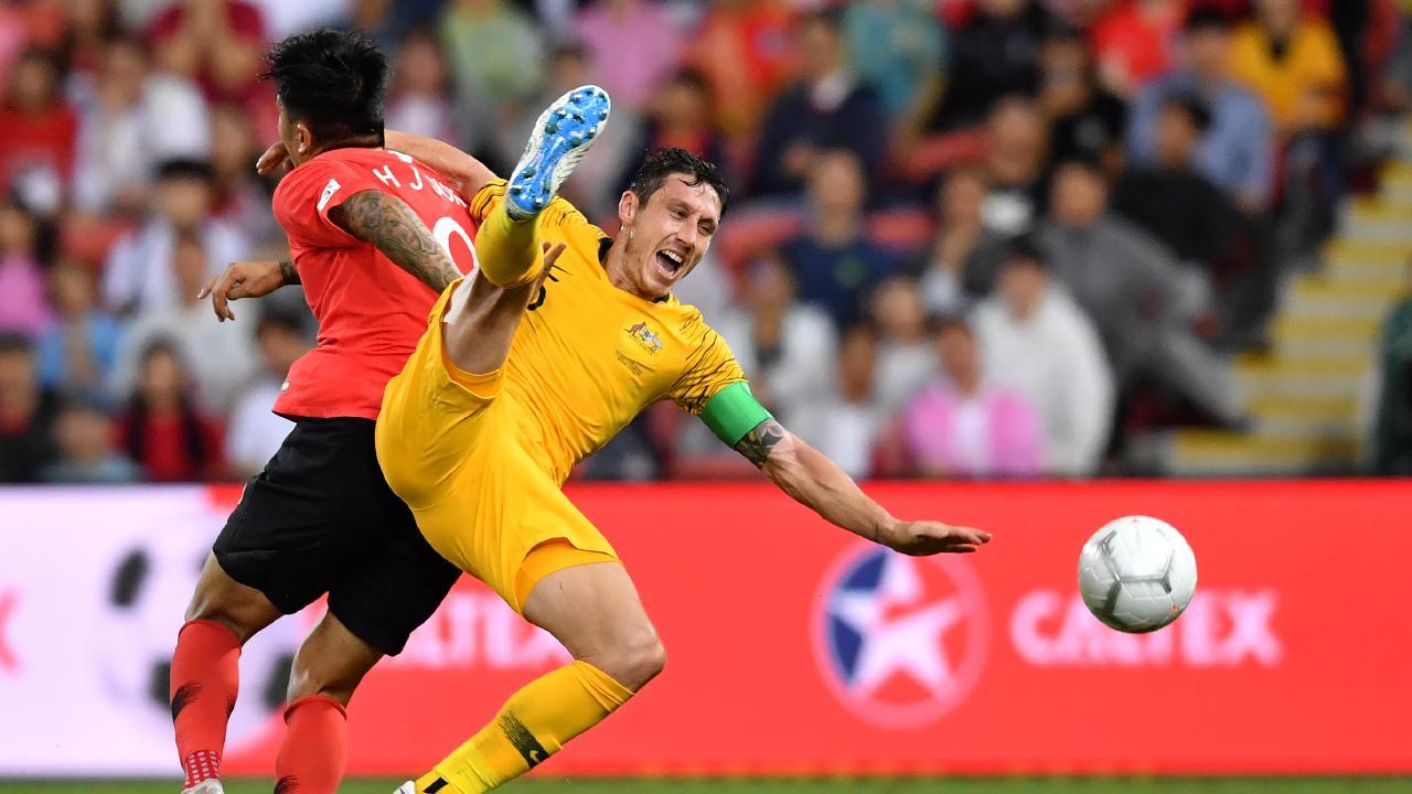 Suk Hyunjun (left) of Korea Republic in action against Mark Milligan (right) of the Socceroos.
