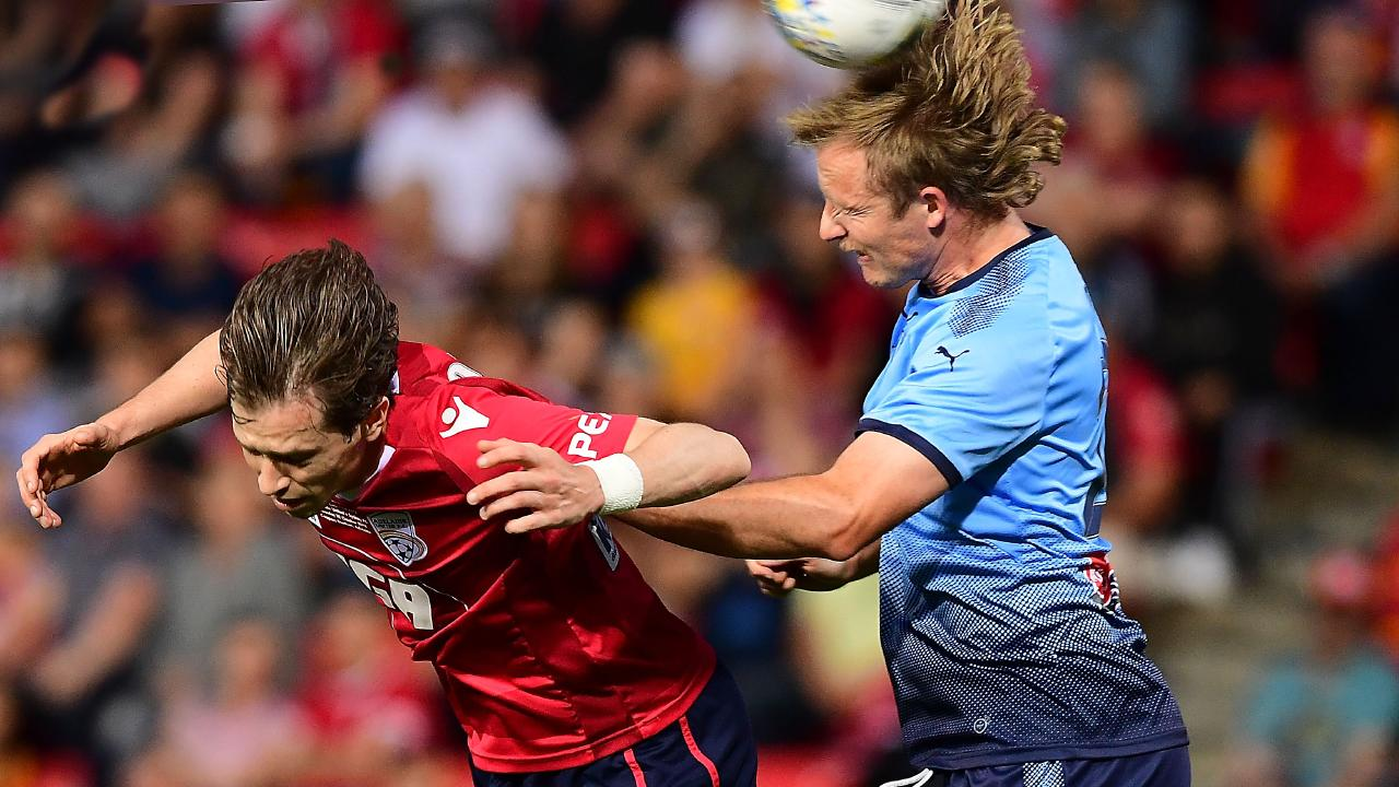 Rhyan Grant of Sydney FC heads over Craig Goodwin of Adelaide United