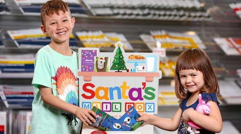 FESTIVE FUN: Flynn and Lilliana get ready to post their Santa Mail envelopes.