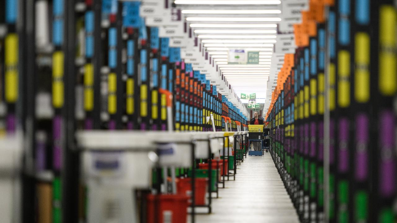 A staff member picks customer orders from the storage shelves at the Amazon Fulfillment Centre in Hemel Hempstead, England, on November 14. Picture: Leon Neal/Getty Images