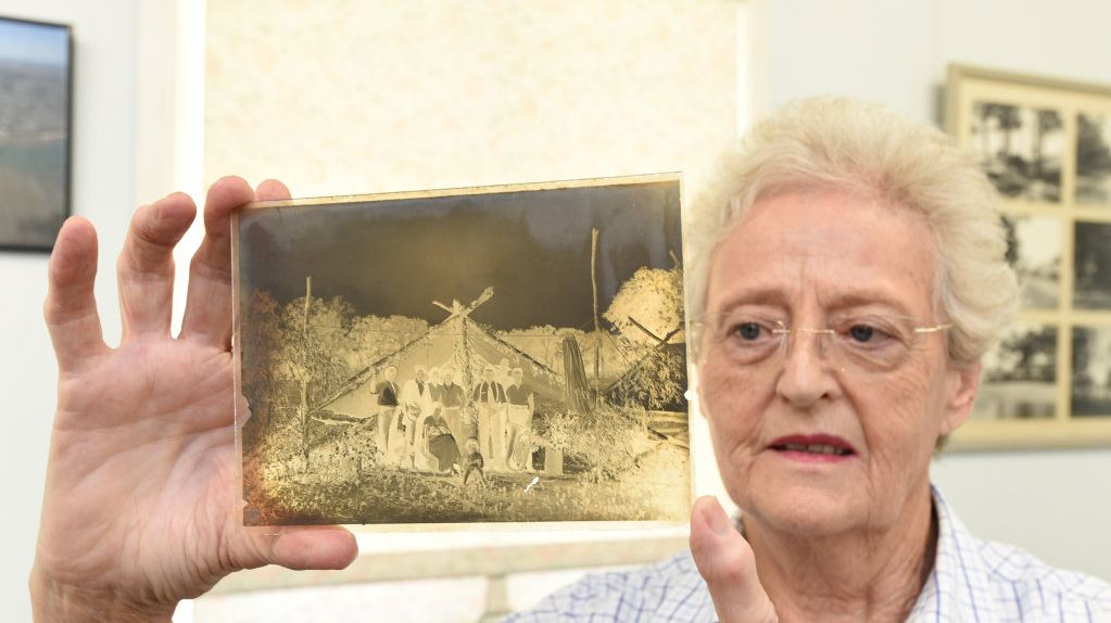 Hervey Bay Historical Village and Museum volunteer Kay French shows off one of the photographic glass negatives that were uncovered at the Hervey Bay dump 20 years ago.