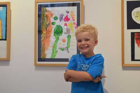 Elliot Fowler with his piece in the Through a Child's Eye exhibition.
