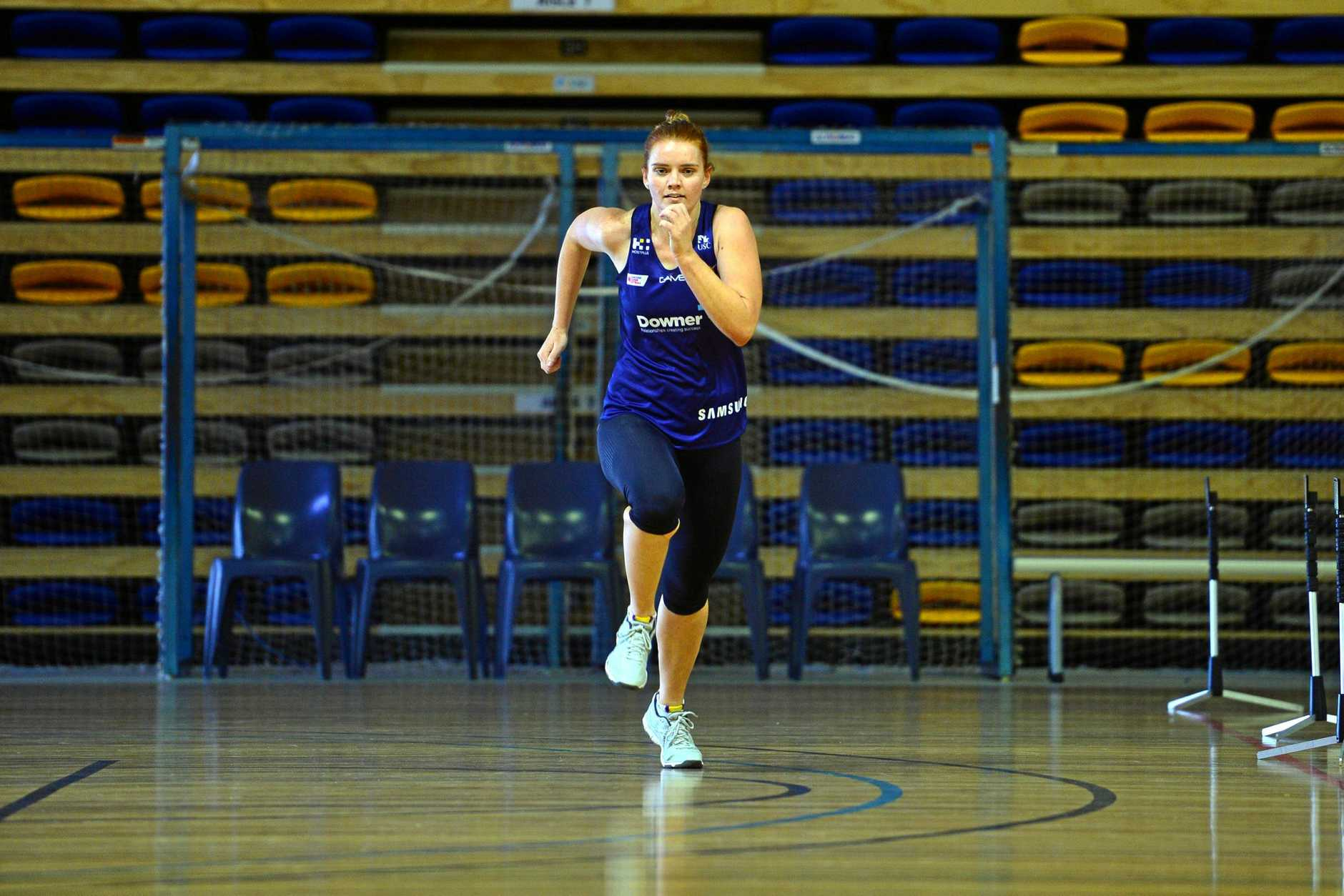 Sunshine Coast Lightning player Stephanie Wood runs through timing gates at Sunshine Coast University under the eye of Mark McKean.