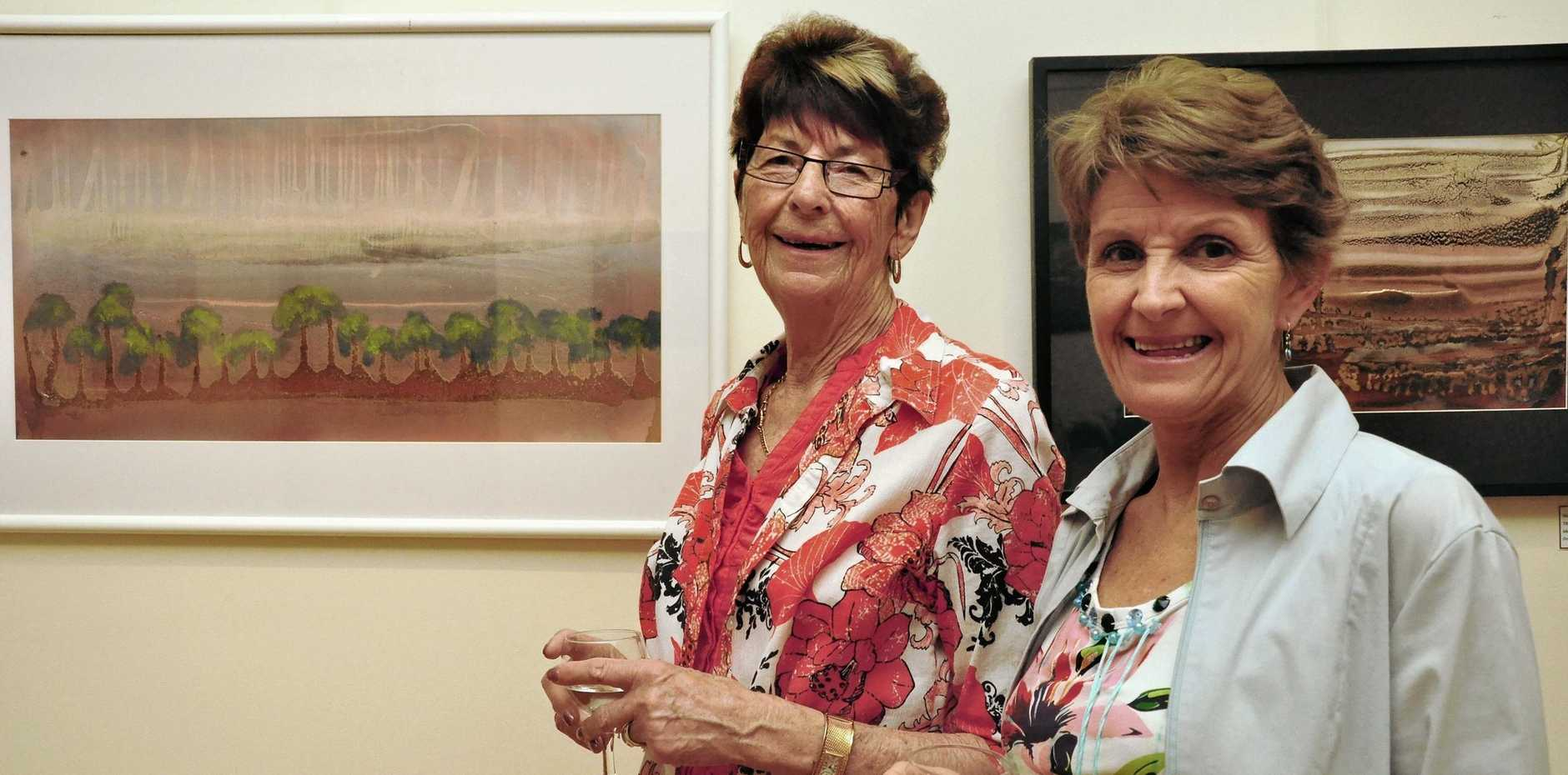 WILL BE MISSED: Alison Iszlaub (left) and Jill Copeland admiring the artwork on display at the Wondai Art Gallery in 2012.