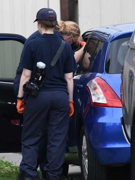 AFP officers examine a car parked in the driveway. Picture: Nicole Garmston